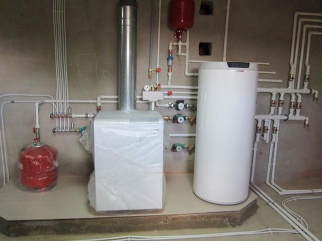 Установленный расширитель отопления (слева).